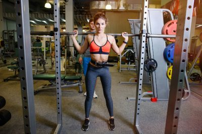 Sporty woman with a barbell accross her shoulders