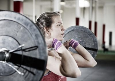 female athlete lifting a barbell with a clean grip