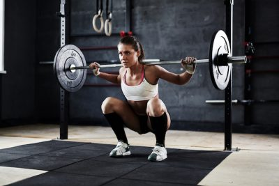 woman performing a deep barbell squat