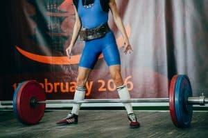 female standing over a barbell at a weight lifting event