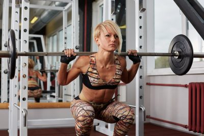 Blonde woman performing barbell squats