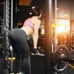 athletic woman training her lower body inside a modern gym