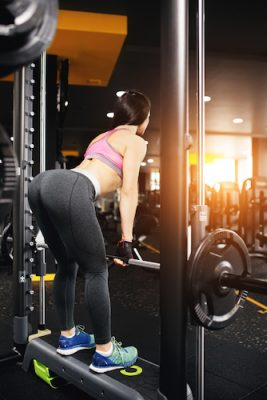 athletic woman training her lower body inside a modern gym