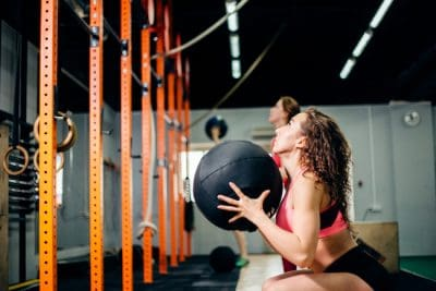 two woman with medicine balls training in gym