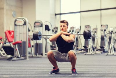 young man training inside a modern gym with fitness equipment in the background