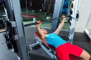 young woman bench pressing at the gym