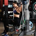 Young woman working out on a Smith machine in a modern gym