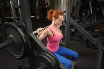 sporty woman doing squats with a barbell