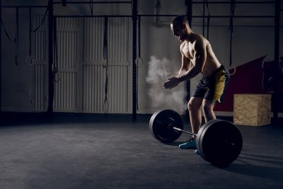 athlete prepairing to lift a heavy barbell off the floor