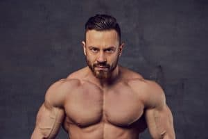 Portrait of shirtless bearded bodybuilder over grey background.