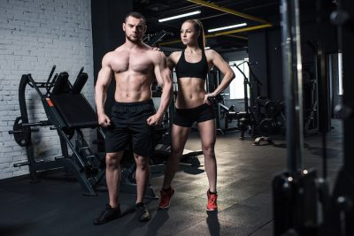 an athletic man and woman stood in the gym weight room