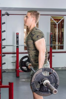 man performing barbell curls in front of a gym rack