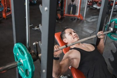 muscular man performing a bench press with a barbell