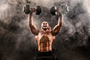 Bald Topless Muscular Man Doing Exercises With Two Dumbbells