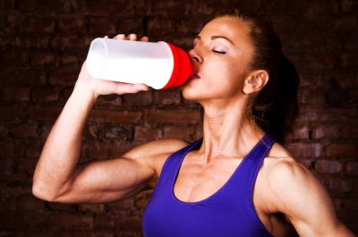 muscular woman drinking a protein shake