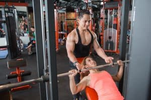 Young woman lifting a barbell with help from her personal trainer